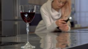 Red wine in a glass on the table, woman holding a bottle on the background. Selective focus on a wine glass, woman enjoying evening at her home. Real estate royalty free stock photography