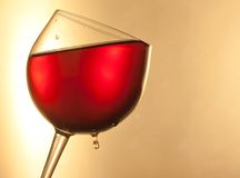 Red wine in the glass tilted with golden drop and space for text Royalty Free Stock Photo