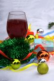 Red wine in the glass, tree branches and Christmas balls on old wooden background, selective.  Stock Image