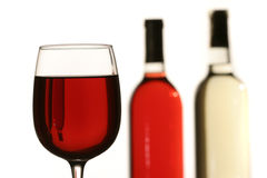 Red wine glass with two bottles. In background Stock Images