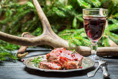 Red wine in a glass and venison on a plate Royalty Free Stock Photography