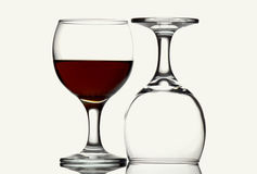 Red wine glass on white background. Two wines glasses, one empty and inverted, one half ful of red wine against white background using bright field lighting Stock Images