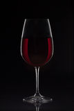 Red wine glass with wine on black background.  royalty free stock images