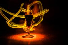 Red wine. Glass of wine. Pouring red wine. Wine glass in fire concept. One glass of red wine with burning fire on black background. Selective focus. Empty space stock photo