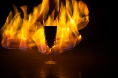 Red wine. Glass of wine. Pouring red wine. Wine glass in fire concept. One glass of red wine with burning fire on black background. Selective focus. Empty space royalty free stock photos