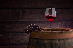 Red wine  glass on wodden barrel. Red wine bottle and wine glass on wodden barrel stock photos