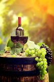 Red wine and glass on wodden barrel. Royalty Free Stock Images