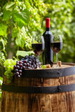 Red wine and glass on wodden barrel. Stock Photos