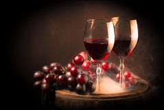 Red wine glass on wooden barrel. Isolated on black gradient royalty free stock image