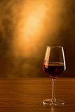 Red wine glass on wooden table and golden background Stock Images
