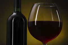 Red wine glass on the yellow background Royalty Free Stock Image