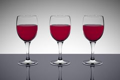 Red wine glasses. Three glasses of red wine on a dark reflective table (3D rendering Stock Image