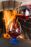Red wine in glasses. Two glasses with red wine at a fireplace Royalty Free Stock Image
