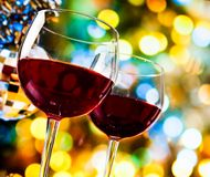 Red wine glasses against colorful bokeh lights and sparkling disco ball background Royalty Free Stock Images