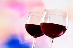 Red wine glasses against colorful unfocused lights background Royalty Free Stock Photography