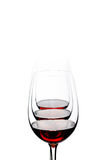Red wine glasses arranged and isolated on white background Stock Photos