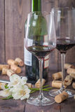 Red wine glasses, bottle and corks Stock Image