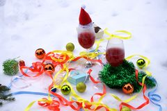 Red wine glasses and christmas balls on snow royalty free stock photos