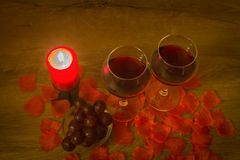 Red wine glasses, grapes, burning candle, and rose leaves on table royalty free stock images