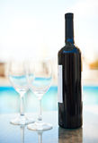 Red wine and glasses near blue water. Bottle of red wine and two glasses near a blue water Stock Images