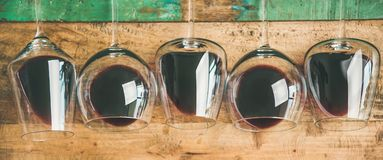 Red wine in glasses over rustic wooden background, wide composition royalty free stock photo