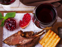 Red wine glasses. Rack of lamb with pomegranate sauce and greens. Royalty Free Stock Photo