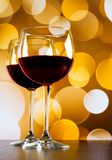 Red wine glasses on wood table against golden bokeh lights background Stock Photo