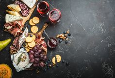 Delicatessen plate. Red wine glasses, wooden boards, cold meat, cheese, fruit, dip. Stone background. Space for text. Delicatessen plate. Mix of different snacks Stock Images