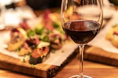 Red wine glasses on a wooden plank with defocused antipasto catering platter at the background royalty free stock photography
