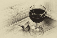 Red wine glasson wooden table. vintage filtered image. black and white style photo Royalty Free Stock Image