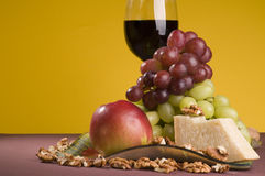 Red wine with grape, apple and cheese on a plate.