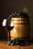 Red wine, grape and barrel. Glass of red wine, dark grape and souvenir barrel on wooden surface royalty free stock photo