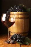 Red wine, grape and barrel. Glass of red wine, dark grape and souvenir barrel on wooden surface stock images
