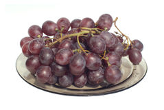 Red wine grape branch on plate isolated on white Royalty Free Stock Image