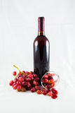 Red wine and grape. A photo of a bottle of red wine that has some grapes around the bottom and a glass is leaning near the bottle Royalty Free Stock Photography