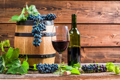 Red wine and grapes in a barrel. On old wooden table Royalty Free Stock Photography
