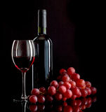 Red wine and grapes. A bottle and a glass of red wine and a bunch of red grapes on black background Stock Images