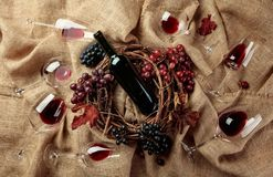 Red wine and grapes on a burlap. Top view stock images