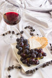 Red wine, grapes and cheese. A composition of red wine, grapes, cheese and bread on a silk silver cloth Stock Images
