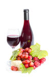Red wine, grapes and cheese. Full glass of red wine, bottle, cheese and grapes with leaves isolated on white background Stock Photo