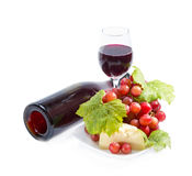 Red wine, grapes and cheese. Full glass of red wine, bottle, cheese and grapes with leaves isolated on white background Royalty Free Stock Photos