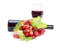 Red wine, grapes and cheese. Full glass of red wine, bottle, cheese and grapes with leaves isolated on white background Stock Photography