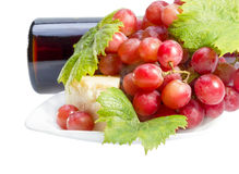 Red wine, grapes and cheese. Full glass of red wine, bottle, cheese and grapes with leaves isolated on white background Royalty Free Stock Photo