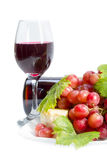 Red wine, grapes and cheese. Full glass of red wine, bottle, cheese and grapes with leaves isolated on white background Stock Images