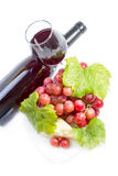 Red wine, grapes and cheese. Full glass of red wine, bottle, cheese and grapes with leaves on white background Stock Images