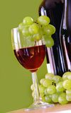 Red wine with grapes cluster over green. Red wine glass with grapes cluster and bottle over green background Royalty Free Stock Photo