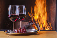 Red wine and grapes at fireplace Stock Images