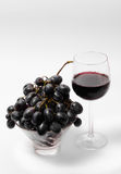 Red wine and grapes. Red wine in a glass and grapes over white-gray background Royalty Free Stock Image