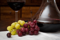 Red wine and grapes. Glass of red wine served from an elegant decanter with fresh red and green grapes Stock Image