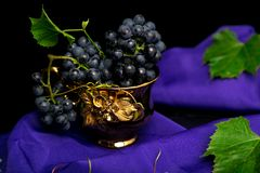 Red wine grapes in golden cup on violet background. Red wine grapes in golden cup on violet background Royalty Free Stock Images